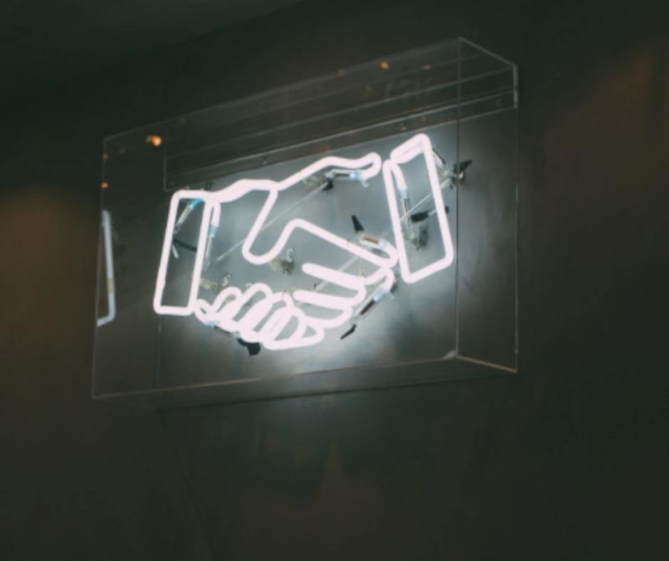 Neon sign of handshake