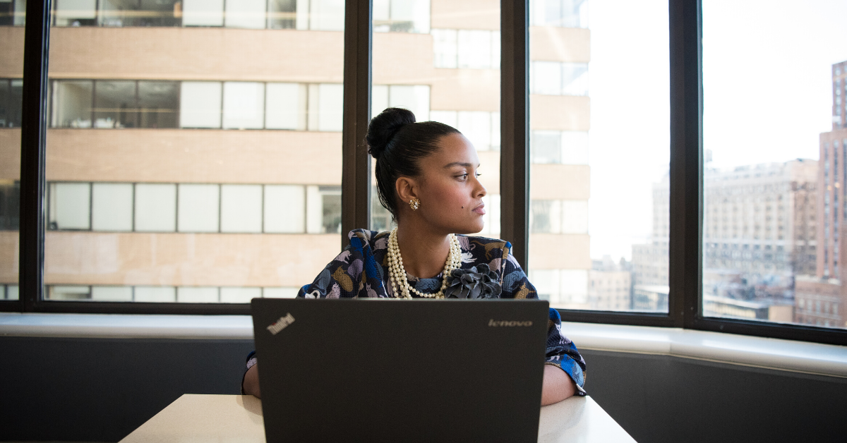 Woman sitting and working on laptop, while staring outside of office windows.