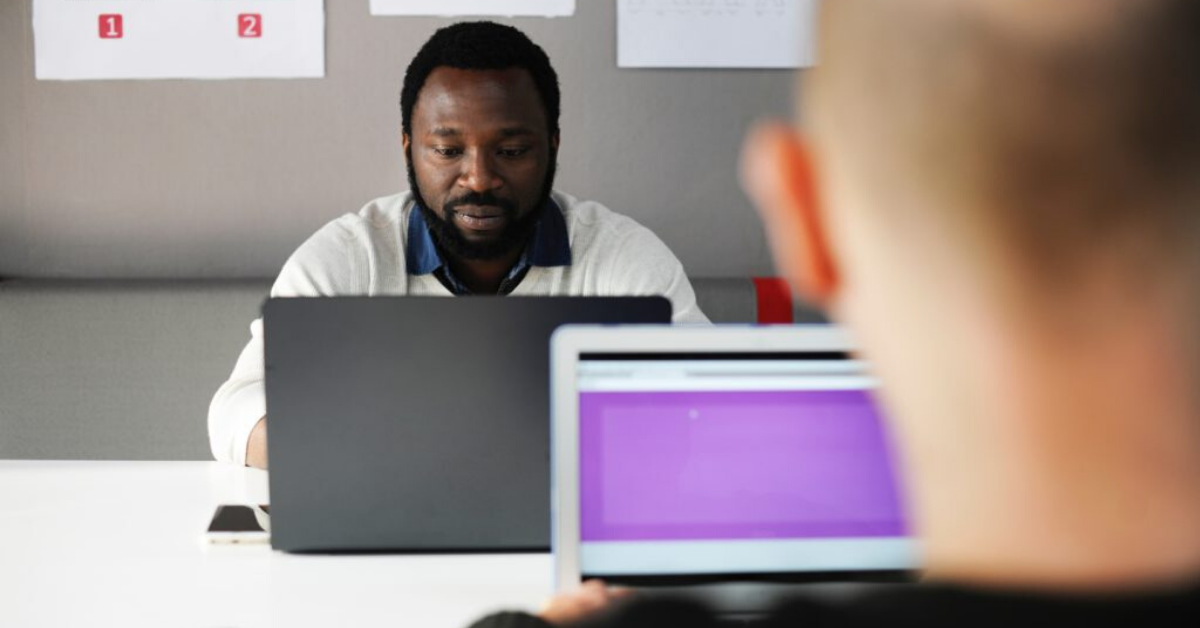 Black man is seen working on laptop. The camera sits behind a white mans head.