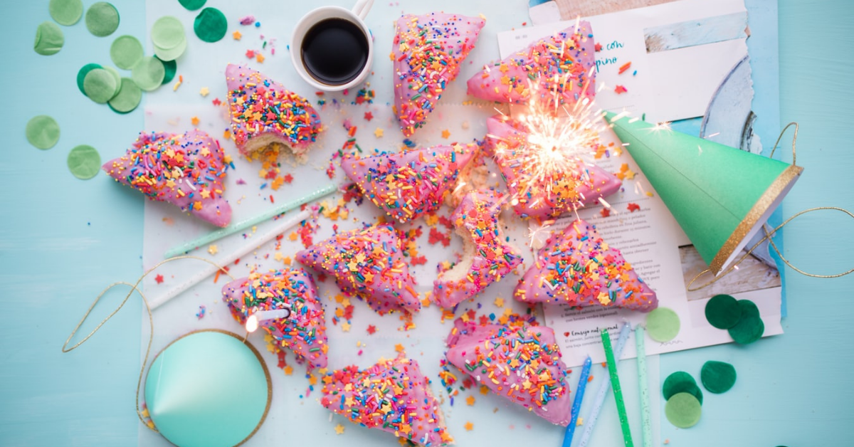 Photo of cake, party hat and confetti on a table