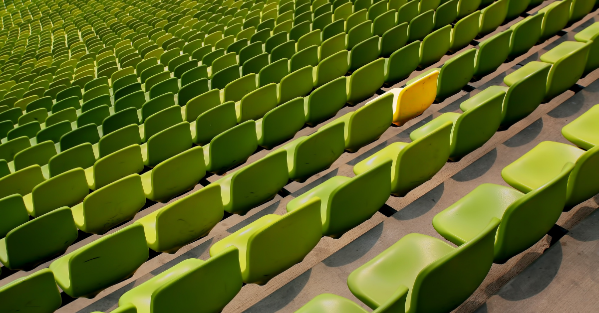 Rows of identical green chairs with one yellow chair.