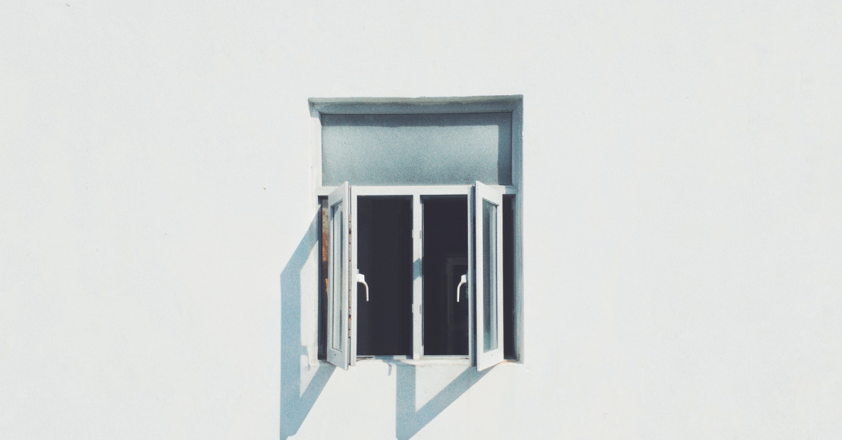 Photo of an open window against a plain white wall.