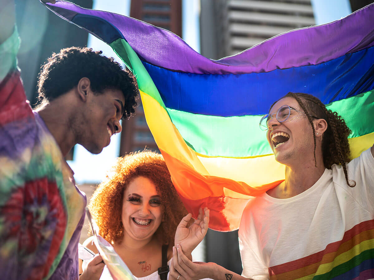 3 people holding a pride flag and laughing