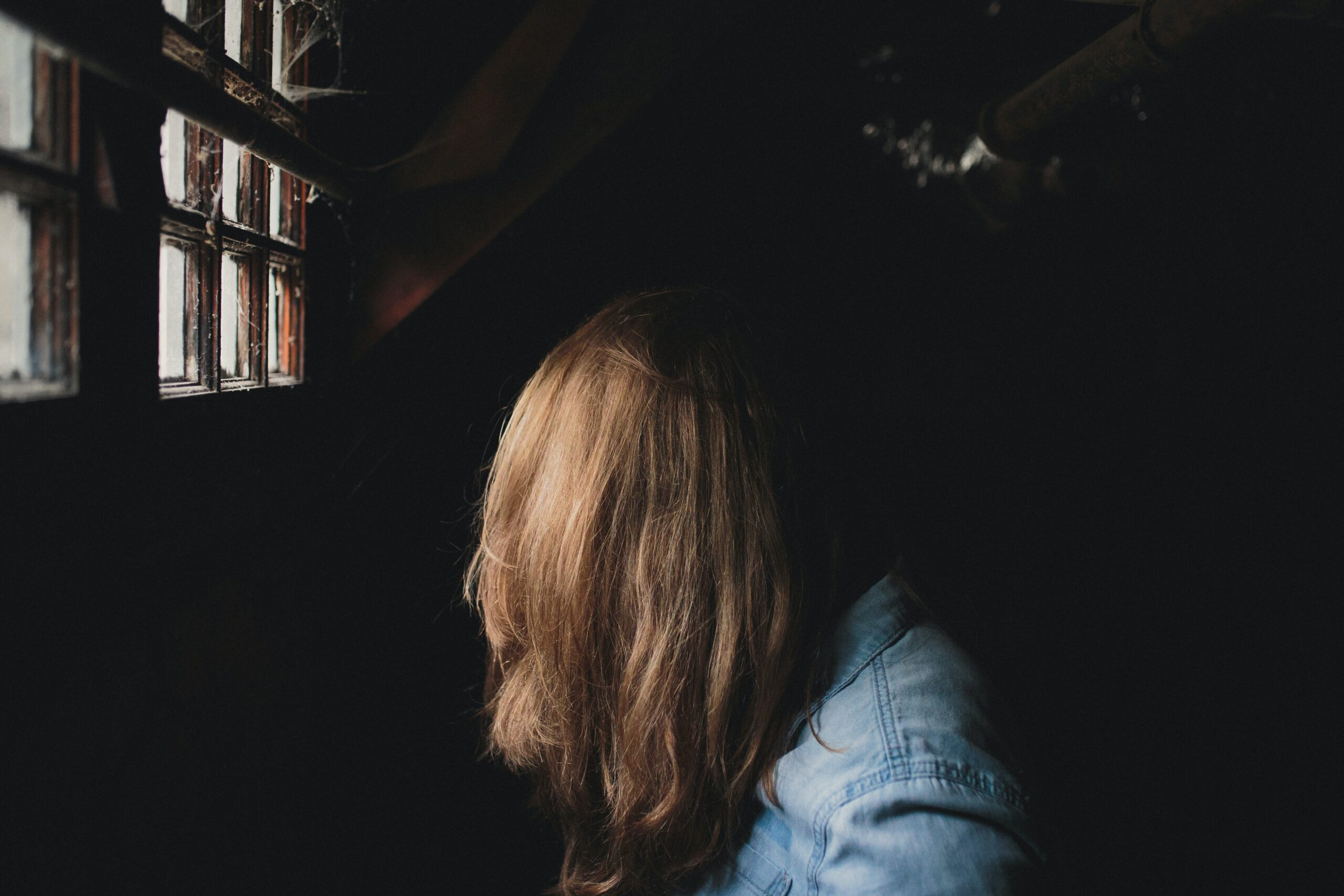 profile of woman with brown hair covering her face looking out window