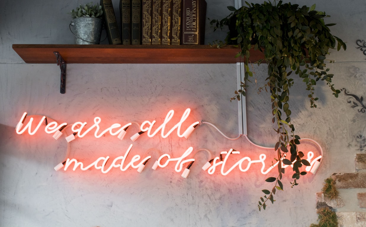 """wall with words on the wall made of pink lights reading, """"we are all made of stories"""""""